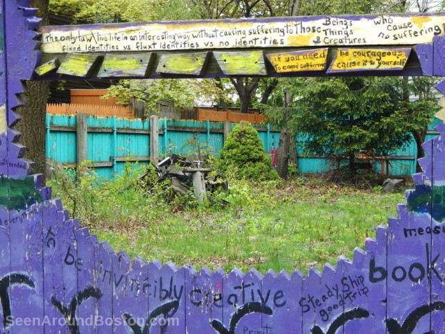 cutaway in purple painted fence, cambridge massachusetts street art