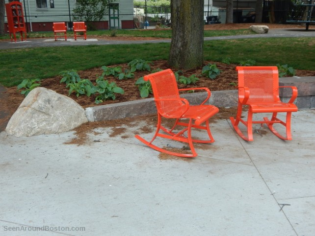 orange rocking chairs in a park in cambridge